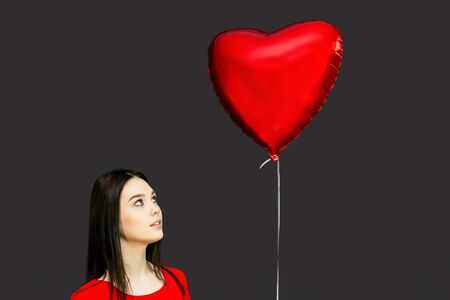 A girl looks at a flying ball. A brunette girl in a red dress looks at a ball in the form of a heart on a black background.
