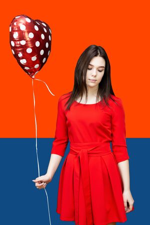 Sad girl with a broken heart A brunette girl with a red heart ball is sad against a bright background of trendy colors of 2020 Stock Photo