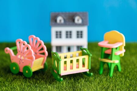 Concept, childhood, crib, highchair, baby carriage accessories and furniture on the grass near the country house.