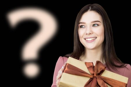 The girl is thinking about her gift, what's there. The brunette girl is holding a gift box in her hands and asks the question what is in it trying to guess what was presented Banque d'images
