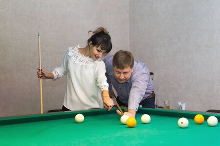 Adult man and a brunette woman stand near a table for a game of billiards. Фото со стока