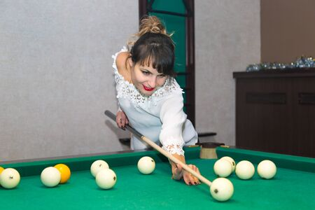 Girl brunette plays billiards. Sport lifestyle A young woman of 30-35 years old beats a cue ball on billiard ball