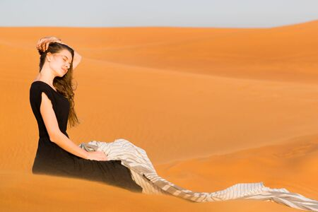 A girl in a black dress sits on the sand in the desert. Young beautiful woman sits tiredly on the hot sand of the desert under the hot rays of the eastern sun. 版權商用圖片