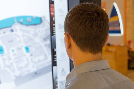 An adult male buyer of a large shopping center is looking for the right store on an electronic map. A man near the interactive map of the supermarket. 版權商用圖片