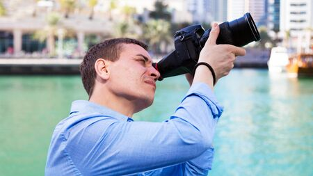 City photographer takes pictures of buildings and architecture. A male tourist photographs the architecture of the European capital.