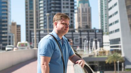 European tourist in a blue shirt on the bridge. Caucasian male blond stands on a pedestrian bridge looking at the river.