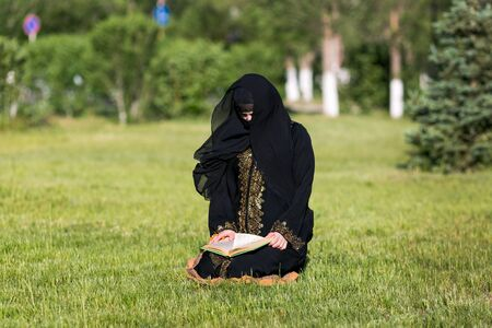 Islamic woman prayer in a city park. Islamic woman performs morning prayer sitting on green grass in a park 스톡 콘텐츠