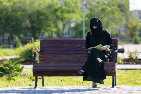 Muslim woman is reading a book on a bench. Islamic girl in national dress is sitting with a book in her hands in a city park.