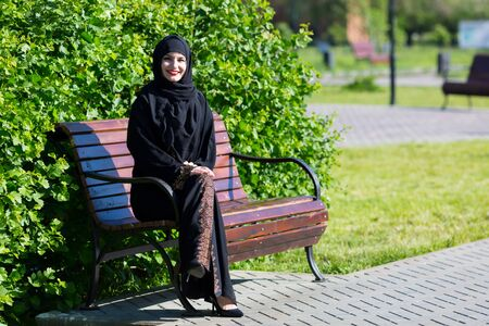 A beautiful young muslim woman is sitting on a bench. Islamic girl smiles broadly, resting on a park bench.