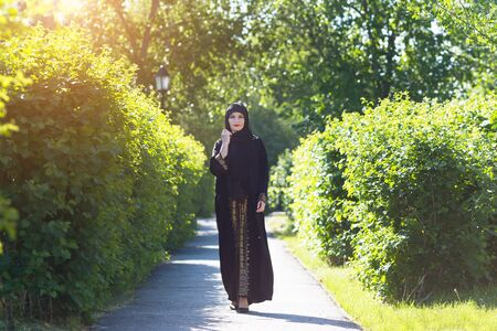 Beautiful confident running muslim woman. A girl in Islamic oriental clothes beautifully walks along the alley among the trees.