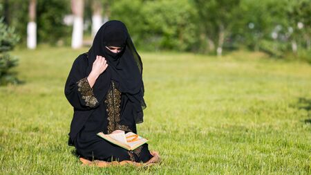Islamic woman prayer in a city park. Islamic woman performs morning prayer sitting on green grass in park.