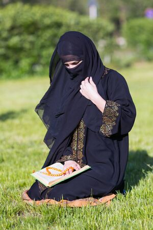 Islamic woman prayer in a city park. Islamic woman performs morning prayer sitting on green grass a park. 스톡 콘텐츠