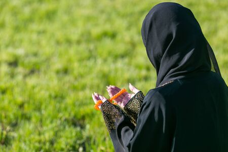 Islamic woman prayer in a city park. Islamic woman, performs morning prayer sitting on green grass in a park