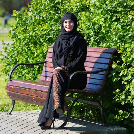 A beautiful young muslim woman is sitting on a bench. Islamic girl smiles broadly, resting on a park bench