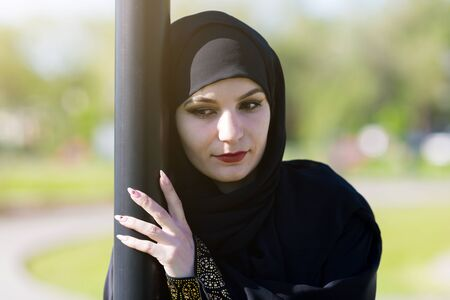 Sad woman in muslim clothes. Islamic girl in black clothes sad alone on street