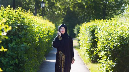 Beautiful confident running muslim woman. A girl in Islamic oriental clothes beautifully walks along the alley among trees 스톡 콘텐츠