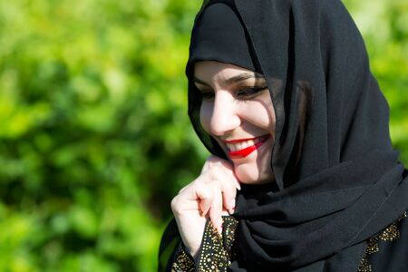Beautiful young muslim woman smiles broadly. Eastern woman in national dress with red lips painted on the street smiling.