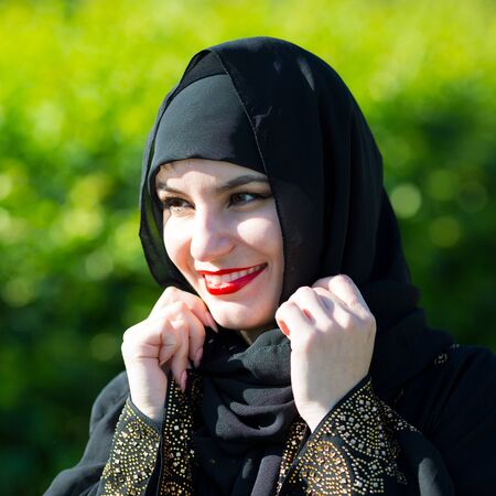 Beautiful young muslim woman smiles broadly. Eastern woman in national dress, with red lips painted on the street smiling.