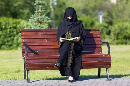 A migrant from the Middle East is sitting on a bench. Arab woman in black national dress is reading a book in a city park 版權商用圖片