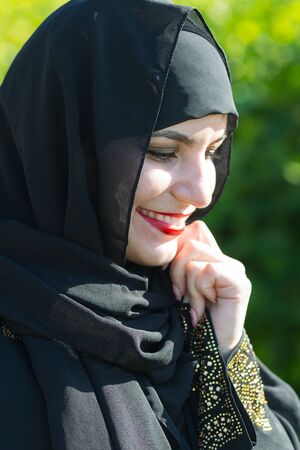 Beautiful young muslim woman smiles broadly. Eastern woman in national dress with red lips painted on the street smiling.,