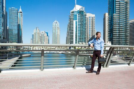 European tourist looks at the views of Dubai. A tourist stands on a bridge over water canal in Dubai.