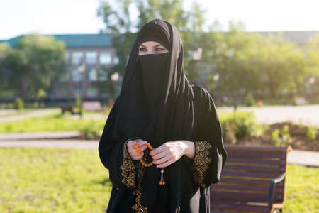 A woman from the east in national Islamic clothes holds religious supplies in her hands. A woman from the east in national Islamic clothes holds religious supplies in her hands spring morning