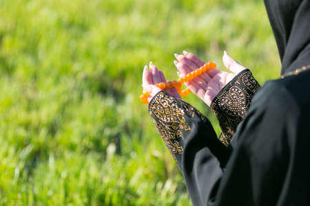 Arab girl praying outdoors sitting on grass in park. Arab girl praying outdoors sitting on grass in park. Hands close up. Archivio Fotografico