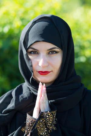 Arab woman in black clothes prays to God. Arab woman in black clothes prays to God against a background of green trees. Archivio Fotografico