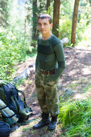 Caucasian male tourist stands on a forest trail. A tourist 35-40 years old stands in the forest on a trekking trail.
