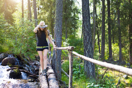 The girl crosses the stream on the fallen logs. A young beautiful tourist walks along the boards through a stormy mountain stream.