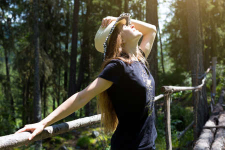 The girl with the hat on her head smiles broadly. A young woman smiles holds hat on her head with her hand on a forest background