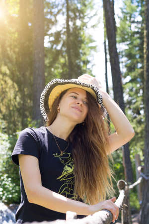 A young girl stands in the forest with a hat on her head. A beautiful young girl holds a hat with one hand, smiles, stands nature.
