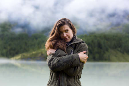 Girl tourist freezes from damp rainy weather in the mountains. A young girl hugs herself by the shoulders from the cold weather in the morning in the mountains. Archivio Fotografico