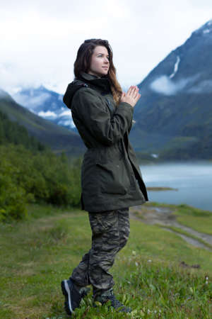 A girl in warm clothes looks at the mountains. A woman in a warm jacket with long hair stands against a background of mountains in the fog in cold damp weather Archivio Fotografico