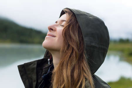 Portrait of a woman in a hood, close-up. Young beautiful woman tourist in a warm jacket and hood on her head against the backdrop of mountains Archivio Fotografico