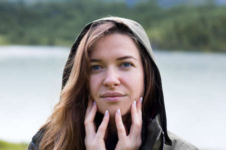 Portrait of a girl with fingers near lips, face. Portrait of a young woman in a hood, brings her fingers to her lips Close-up