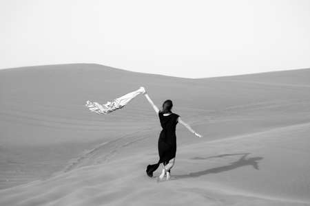 A lonely girl goes down the sand dunes. Caucasian woman in a black dress descends from a mountain in the desert. Black and white