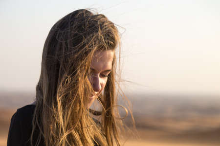 Caucasian young woman with long hair in a black dress at sunrise in the desert. Archivio Fotografico