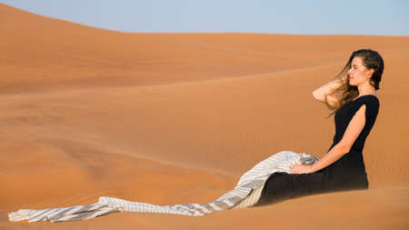 A woman of 20-25 years old in a black dress sits on the warm sand of desert. A cute caucasian girl is resting in the sun.