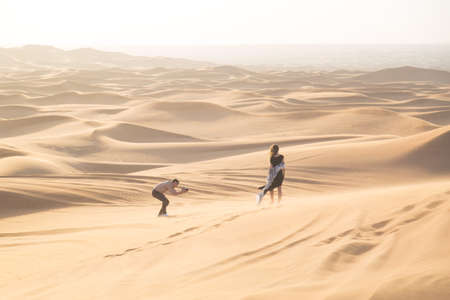 Exclusive photo shoot of a woman in the desert. Magazine advertising filming. The work of the photographer and model in the desert of Dubai
