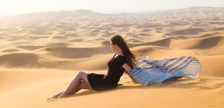 A cute caucasian girl is resting in the sun. A woman of 20-25 years old in a black dress sits on the warm sand of the desert.