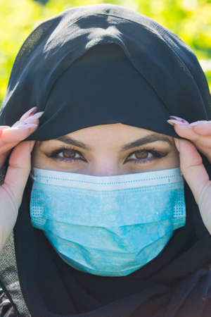 Oriental woman in black clothes in a protective medical mask Virus protection