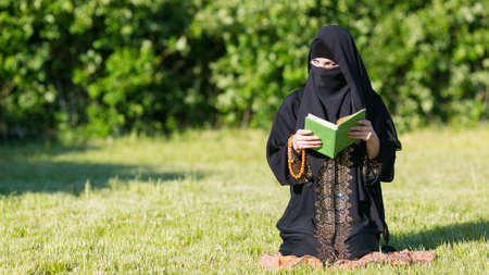 A woman from the East performs morning prayer while sitting in a park green grass.