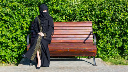 Arab woman migrant from the Middle East in black national clothes is sitting on a bench city park.