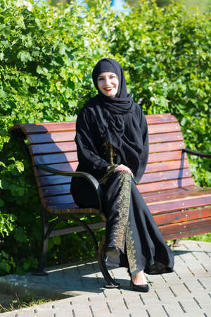 Eastern woman with a beautiful smile is resting in the park. Archivio Fotografico
