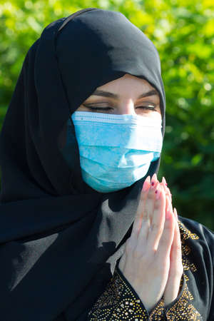 Muslim girl a protective medical mask prays to God during self-isolation and viral quarantine.