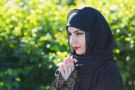 Arab woman black clothes prays to God against a background of green trees. Archivio Fotografico