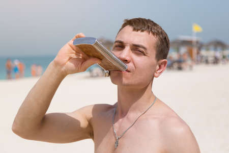 A 35-40 year old man drinks strong alcohol from an iron flask while relaxing on a city beach.