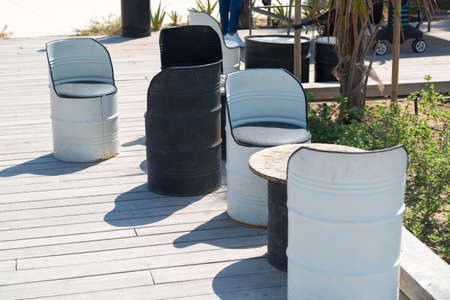 Furniture in a street cafe in the form of barrels Barrels of 200 liters of oil and petroleum products are used as furniture for chairs in the restaurant.