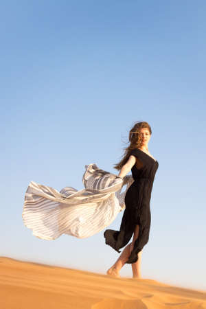 Caucasian woman in a black dress descends from a mountain in the desert. A lonely girl goes down the sand dunes.